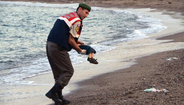 Un soldado europeo levanta el cadáver de un niño sirio.