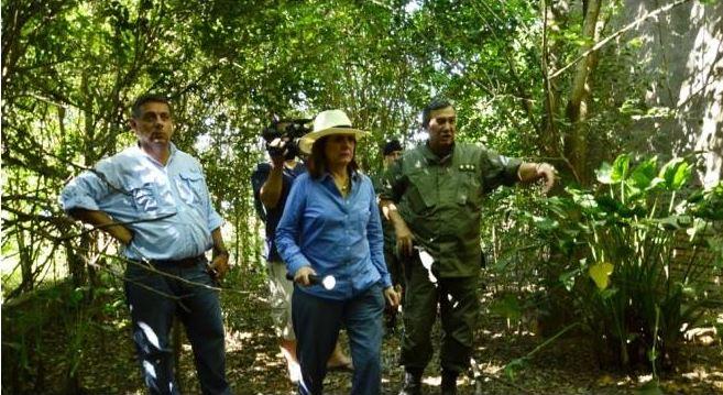 La Ministra Bullrich buscando a los prófugos en un bosque de Santa Fé, de día, con sombrero de picnic y linterna prendida.