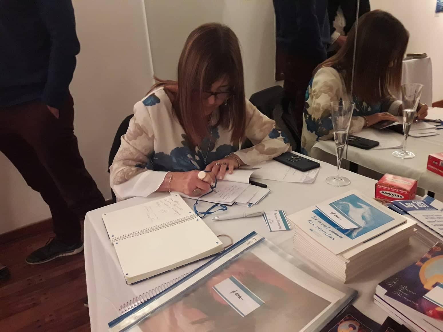 Patricia Alcetegaray firma sus libros en la presentación individual de pintura.