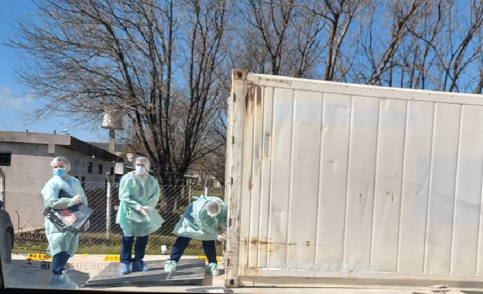 En un Hospital modular de la Provincia de Buenos Aires un grupo de enfermeros ingresan en un acoplado frigorífico esperando que se trasladen cadáveres.